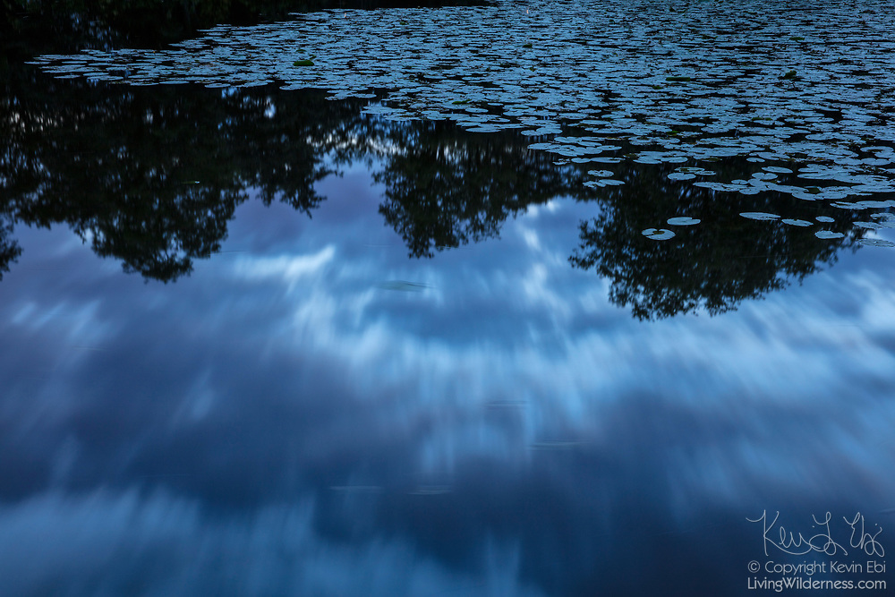 A long exposure captures the motion of dark storm clouds, which are reflected on a large pond, partially covered in water lilies, in Parc des Sources in Brussels, Belgium. The public park is known for its numerous springs — called sources, in French — which provide drinking water to the surrounding area. Parc des Sources is one of six major parks that are connected in an ecological corridor in Brussles. In Dutch, Parc des Sources is called Bronnenpark.