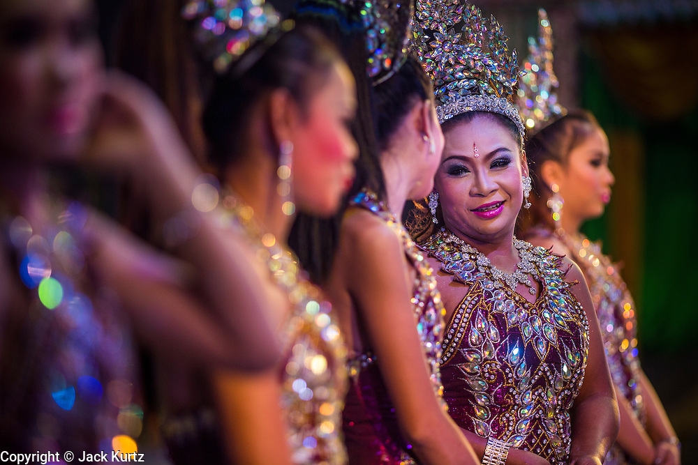19 JANUARY 2014 - BANGKOK, THAILAND:  A mor lam show in Khlong Tan Market in Bangkok. Mor Lam is a traditional Lao form of song in Laos and Isan (northeast Thailand). It is sometimes compared to American country music, song usually revolve around unrequited love, mor lam and the complexities of rural life. Mor Lam shows are an important part of festivals and fairs in rural Thailand. Mor lam has become very popular in Isan migrant communities in Bangkok. Once performed by bands and singers, live performances are now spectacles, involving several singers, a dance troupe and comedians. The dancers (or hang khreuang) in particular often wear fancy costumes, and singers go through several costume changes in the course of a performance. Prathom Bunteung Silp is one of the best known Mor Lam troupes in Thailand with more than 250 performers and a total crew of almost 300 people. The troupe has been performing for more 55 years. It forms every August and performs through June then breaks for the rainy season.              PHOTO BY JACK KURTZ