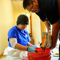 112213  Adron Gardner/Independent<br /> <br /> Thomasina Hayes mixes as Eli Etcitty<br /> pours a new bucket of tile adhesive for improvements to the United Navajo Way in Window Rock Friday.
