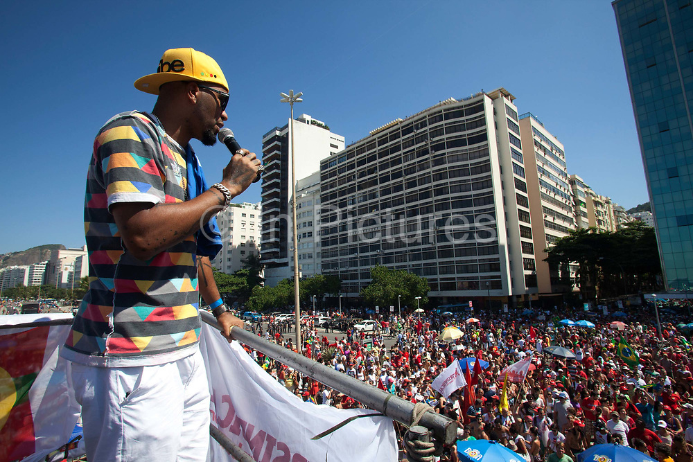 Male singer addressing the crowd from atop a sound system truck at the anti impeachment protest demonstration on April 17th 2016 in Rio De Janeiro. This was the day of the impeachment vote for Brazils president Dilma Roussef, thousands took to the streets across the country. Here, protests in Copacanbana were held, organised by independent community music organisations Rhythm of the Favela, Apa-funk, Furaco 2000, in associaiton with the Workers Party PT.