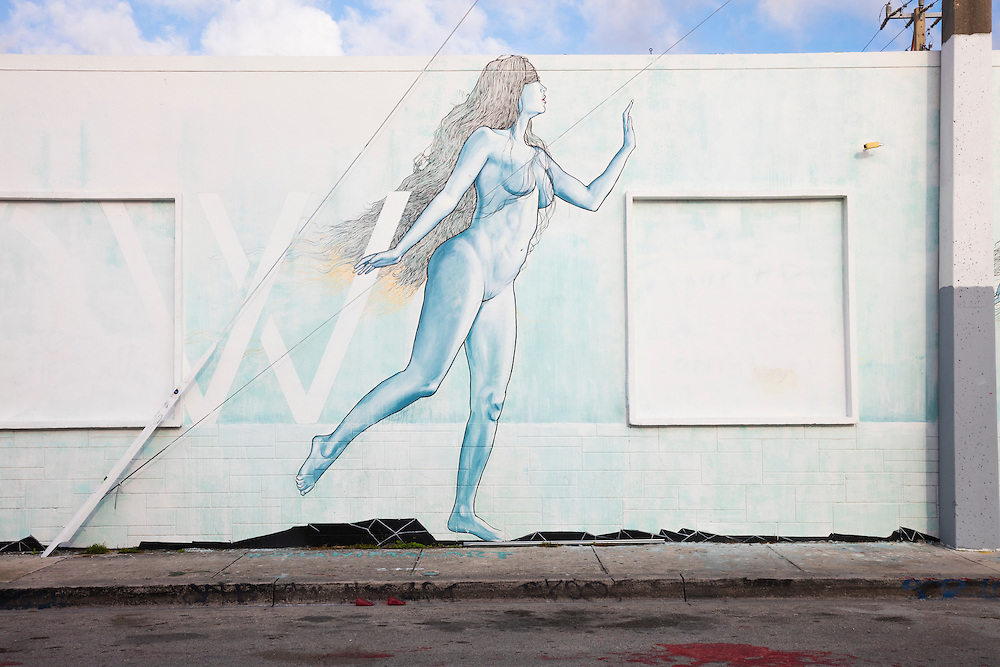 A softly-colored mural in Miami's Wynwood arts district depicts  a nude woman, perhps the Eve to the Adam-like figure painted on an adjacent wall