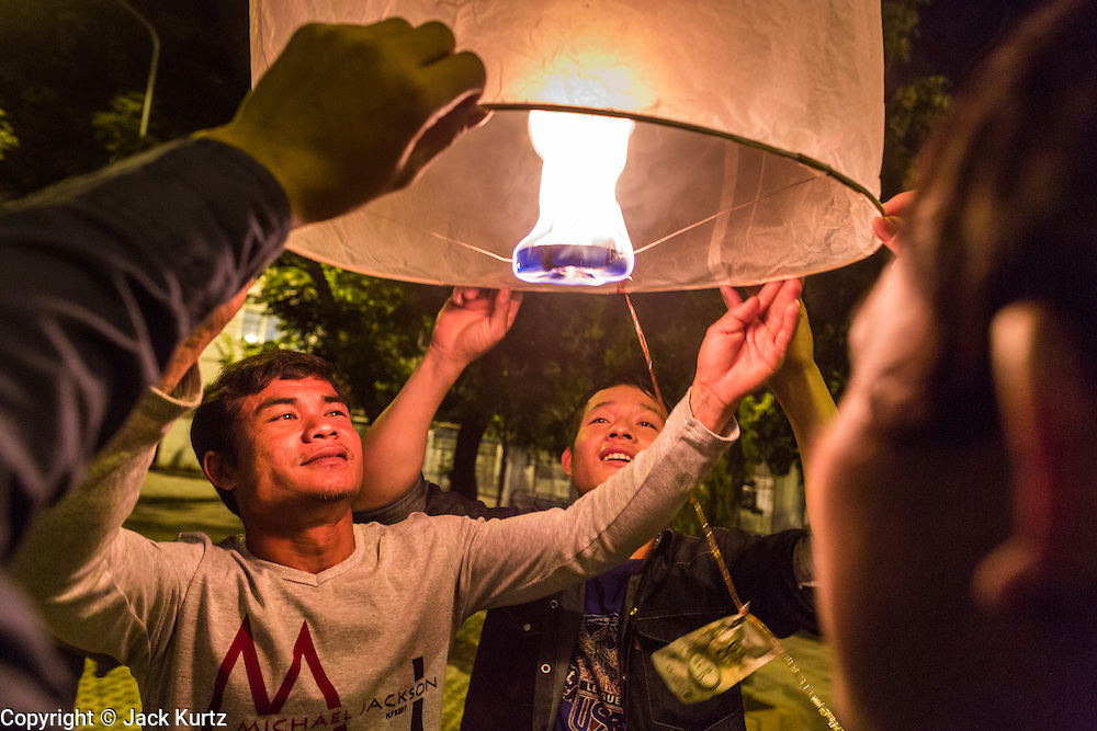 "17 NOVEMBER 2013 - BANGKOK, THAILAND: Thai laborers from northern Thailand luanch  a Yi Peng lantern on Loy Krathong near Wat Yannawa in Bangkok. The Yi Peng lanterns are Loy Krathong tradition in Chiang Mai but they are becoming more popular  in Bangkok and central Thailand. Loy Krathong (also written as Loi Krathong) is celebrated annually throughout Thailand and certain parts of Laos and Burma (in Shan State). The name could be translated ""Floating Crown"" or ""Floating Decoration"" and comes from the tradition of making buoyant decorations which are then floated on a river. Loi Krathong takes place on the evening of the full moon of the 12th month in the traditional and they do this all evening on the 12th month Thai lunar calendar. In the western calendar this usually falls in November. The candle venerates the Buddha with light, while the krathong's floating symbolizes letting go of all one's hatred, anger, and defilements       PHOTO BY JACK KURTZ"
