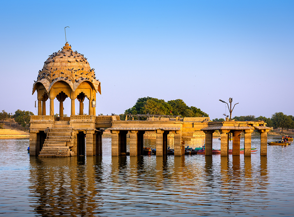 """JAISALMER, INDIA - CIRCA NOVEMBER 2018: View of Gadsisar Lake in Jaisalmer. This is a scenic rainwater lake surrounded by the small temples and shrines of Amar Sagar. Jaisalmer is also called """"The Golden City, and it is located in Rajasthan. . The town stands on a ridge of yellowish sandstone, and is crowned by the ancient Jaisalmer Fort."""