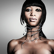 A young model with barbed wire wrapped around her neck.