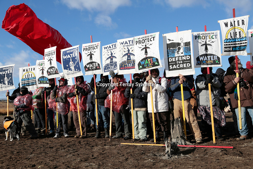 Opponents of the Dakota Access oil pipeline hold signs during a demonstration on a tributary of the Missouri River on November 18, 2016. Cannon Ball, North Dakota, United States.