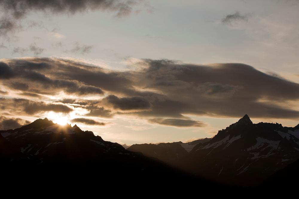 USA, Alaska, Katmai National Park, Kukak Bay, Setting sun lights clouds above mountain peaks on late summer evening