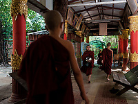 YANGON, MYANMAR - CIRCA DECEMBER 2017: Monks on a temple close to Yangon getting ready for lunch.