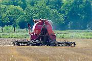 Nederland, Kekerdom, 24-8-2016 Een loonwerker rijdt met een tractor over het land om mest in de grond, bodem te injecteren. Op het perceel stond graan en dat is kort geleden geoogst. De injecteermachine wordt steeds gevuld vanuitt een gesloten laadbak waar vrachtwagens gier in pompen. Vervolgens wodrt het dus naar de tractor en op het land uitgereden . Open gieren mag niet meer vanwege de hoge ammoniak uitstoot. A farmer is riding out liquid manure. The stale is injected into the soil , ground because of the environmental rules against ammonia emission. Foto: Flip Franssen