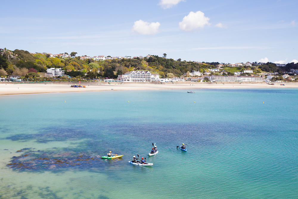 People kayaking on a calm sunny day at St Brelade's Bay, a popular beach with tourists, in Jersey