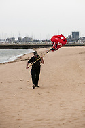 A lone protestor walks along St Kilda Beach with an upside down Red Ensign Australian flag during the Sack Daniel Andrews Protest that stared in Fawkner Park. Parts of the community are looking to hold the Victorian Premier accountable for the failings of his government that led to more than 800 deaths during the Coronavirus crisis. Victoria has recorded 36 days Covid free as pressure mounts on the Premier Daniel Andrews to relax all remaining restrictions. (Photo by Michael Currie/Speed Media)