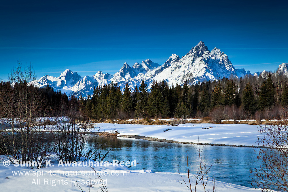 Snow covered Grand Teton Range in Grand Teton National Park, WY on a sunny morning.  Snake River and snowy river bank are in the foreground.