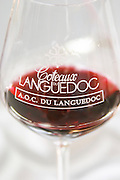 Wine tasting glass against a white background filled with red wine and engraved with the text Coteaux du Languedoc AOC du Languedoc