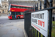 A red London bus passing by the street sign to Parliament Square on the 25th of May 2021 in Westminster, London United Kingdom.  Parliament square is a large open green space right outside the House of Commons, home of the UK government.