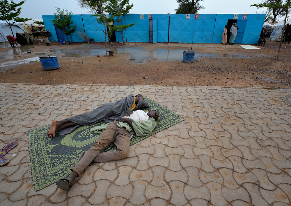 Young men sleep on the ground in a camp in Mopti, Mali, for families displaced by the fighting in the north of the country. Islamist rebels seized control of Timbuktu and other areas of the north in 2012, but were chased out in early 2013 by French troops. Yet many displaced and refugee families have yet to return, preferring to wait for better security and improved economic conditions in the north.