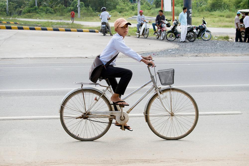 Een jongen fietst door Phnom Penh.
