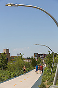 Bicyclists on the 606 elevated bike trail, green space and park built on the old Bloomingdale Line in the Wicker Park neighborhood of Chicago, Illinois, USA