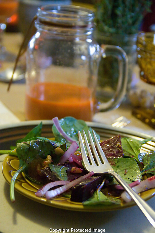A plate of beet root salad with mustard vinaigrette with carrot ginger juice to drink.