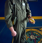 A US Navy airman stands holding a recently-bought hot dog from a food dispenser at the Naval Air Station Sigonella, Sicily Italy. Wearing a green flying suit, the snack is wrapped in a napkin and its chemically-enhanced yellow mustard echoes the stripes and badge of his squadron. Home to over 5,000 military and civilian personnel including family members, Sigonella is an outpost for American nationals who have the luxuries from home freighted out to their remote mission, a hub of naval air operations in the Mediterranean Sea and home comforts keep up morale. Picture from the 'Plane Pictures' project, a celebration of aviation aesthetics and flying culture, 100 years after the Wright brothers first 12 seconds/120 feet powered flight at Kitty Hawk,1903.