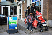 A British family leave the Trussell Trust Kingston foodbank having collected their emergency food supply from the charity.  The woman uses her son's push-chair to take the food home, while he walks beside. They are smiling as they are relieved to have sufficient food for the whole family for the next few days.  The food has been donated to the foodbank through schools, churches and individuals.  In 2012-13 foodbanks fed 346,992 people nationwide. Of those helped, 126,889 were children.  In response to the Government cuts to welfare, foodbanks have experienced a significant increase in demand and in September 2013, Kingston foodbank provided food for their 5,000th person.