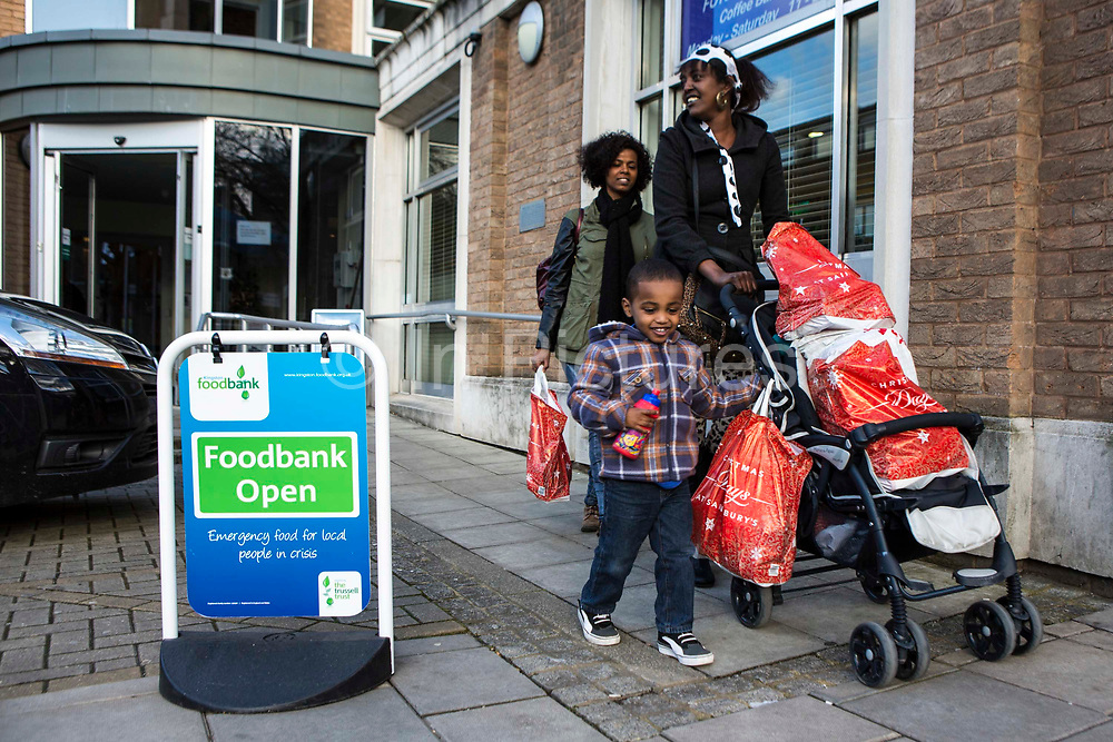 A British family leave the Trussell Trust Kingston foodbank having collected their emergency food supply from the charity.  The woman uses her son's push-chair to take the food home, while he walks beside. They are smiling as they are relieved to have sufficient food for the whole family for the next few days.  The food has been donated to the foodbank through schools, churches and individuals.  In 2012-13 foodbanks fed346,992 people nationwide. Of those helped, 126,889 were children.  In response to the Government cuts to welfare, foodbanks have experienced a significant increase in demand and in September 2013, Kingston foodbank provided food for their 5,000th person.