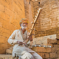 A man plays the Ravanahatha, a traditional string instument, under the golden walls of Jaisalmer Fort, Rajasthan, India.