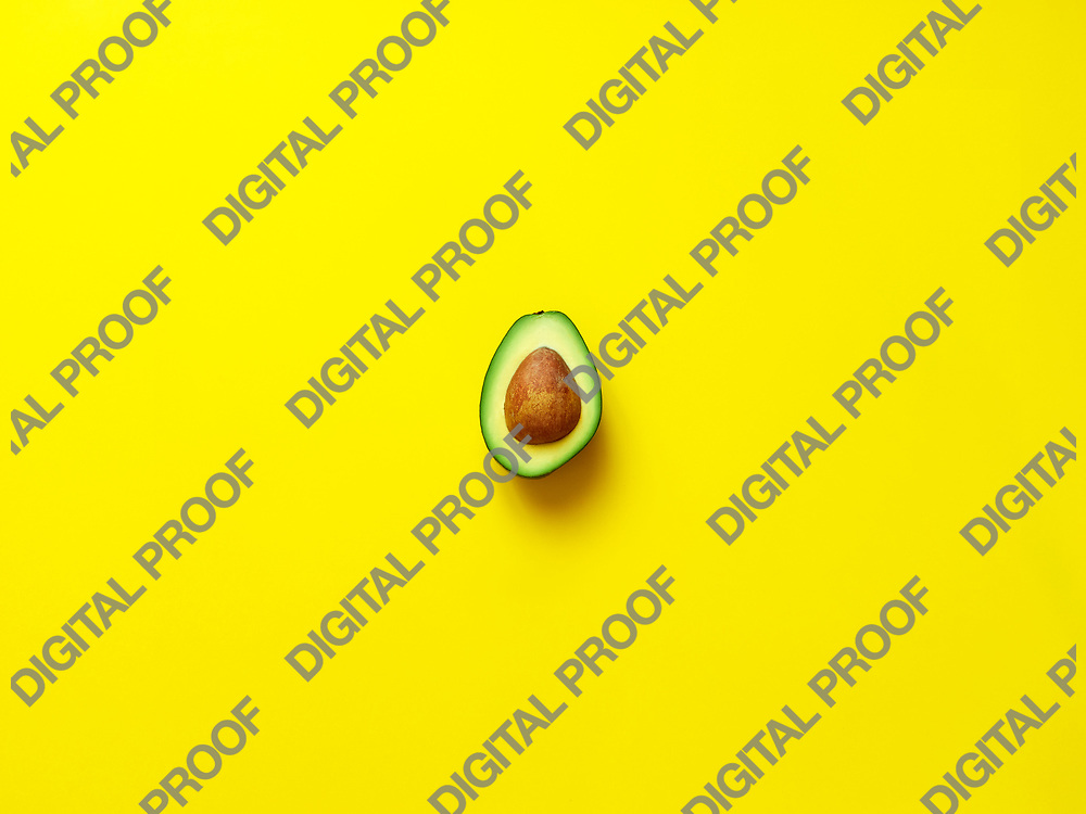 Avocado with seed isolated in yellow background viewed from above - flatlay look