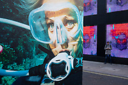 Advertising poster of a woman wearing scuba diving breathing aparatus interacts with brightly coloured screens and passing people on a corner on Oxford Street on 21st January 2020 in London, England, United Kingdom. Oxford Street is a major road in the West End of London. It is Europes busiest shopping street, with around half a million daily visitors, and has approximately 300 shops.