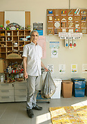 CAPANNORI, Tuscany,, founder of Centro di Ricerca Rifiuti Zero in his office.  a little musuem of design mistakes, above alternatives products, on hirs right  a kind of black list of non reciclyng packages