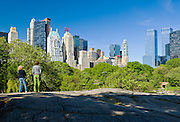 People enjoying Central Park, New York City in springtime with view of Midtown Manhattan Skyline, including the Time Warner Center at right.