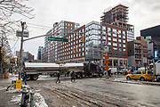 A large silver truck crosses the intersection of East Houston and Bowery Lower East Side, New York City, New York, Unites States of America.  The green Bowery New York Street Sign has been decorated with the word David in tribute to the rock star David Bowie who died in January 2016, the same month that the city experienced a record breaking snowstorm, some snow piles can still be seen on the side of the road.