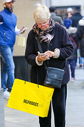 © Licensed to London News Pictures. 23/12/2018. London, UK. A woman with Selfridges bag looking at her mobile phone on Oxford Street. Last minute Christmas shoppers take advantage of pre-Christmas bargains in London's Oxford Street. Fewer shoppers have been reported shopping in Britain's high streets as online sales increase. Photo credit: Dinendra Haria/LNP