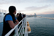Passengers of the Grimaldi Lines Cruise Barcelona look at the port of Barcelona, in Spain, on Sunday, June 9, 2013.  Photographer: Víctor Sokolowicz/Bloomberg.