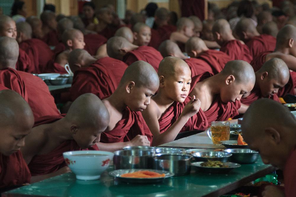 Novice monks eating mid-day meal in Mandalay, Myanmar (Burma).