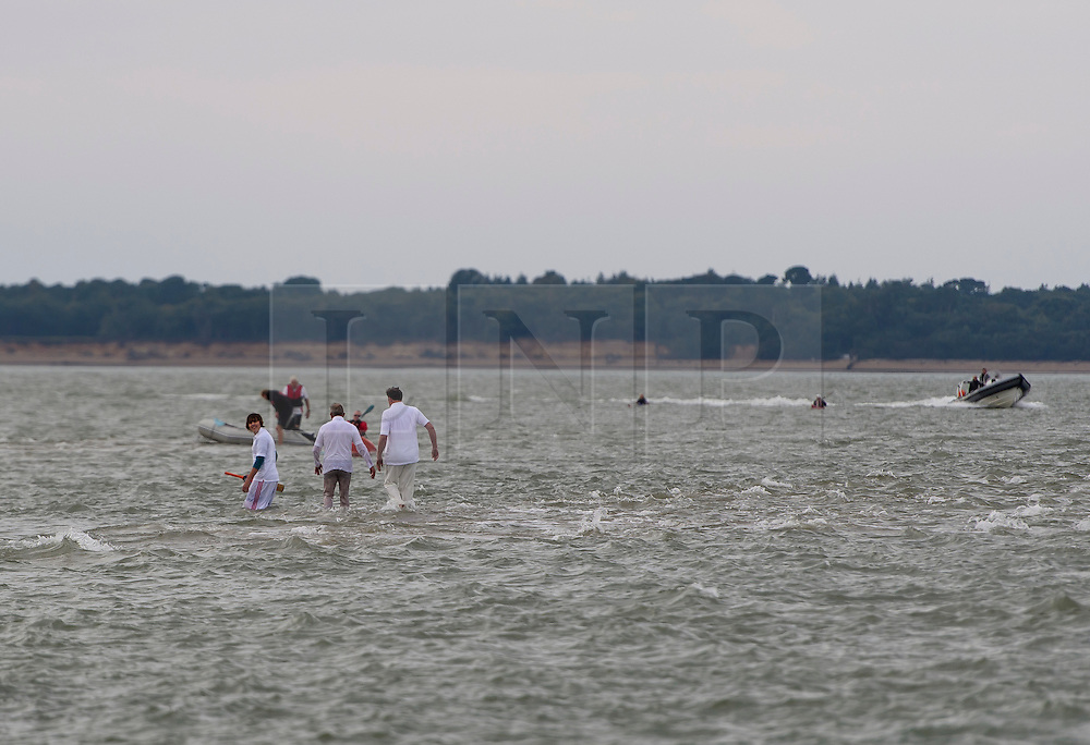 © Licensed to London News Pictures. 18/09/2016. Portsmouth, UK. Players wade through sea water to the pitch. Teams take part in the  Bramble Bank Cricket Match in the middle of The Solent strait on September 18, 2016. The annual cricket match between the Royal Southern Yacht Club and The Island Sailing Club, takes place on a sandbank which appears for 30 minutes at lowest tide. The game lasts until the tide returns. Photo credit: Ben Cawthra/LNP