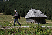 With the help of sticks, a walker makes his way past a mountain hut alongside the stony road in Dolina Chocholowska, a hiking route in the Polish Tatra mountains, on 17th September 2019, near Zakopane, Malopolska, Poland.