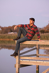 man at sunset on a dock by a peaceful bay