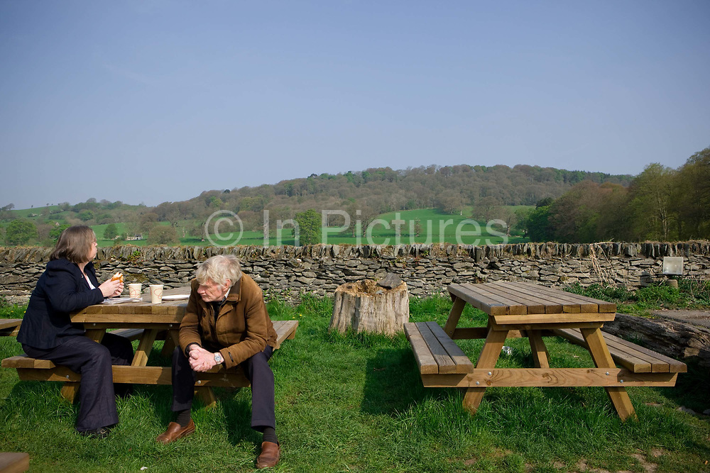 A couple sit at a picnic bench in the grounds of the rural Rhug Organic Farm Cafe on the 20th April 2011 in Corwen in the United Kingdom.