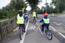 Children cycling to school accompanied by a parent,