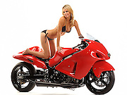 Beautiful blond girl in a bikini on a 2006 Hayabusa drag racing motorcycle on white background.  No logos on bike.