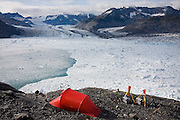 Shad O'Neel, a glaciologist with theUSGS, relaxes at camp overlooking the terminus of the Columbia Glacier, near Valdez, Alaska. To the right are time lapse cameras, documenting in unprecedented detail the glacier's rapid retreat.