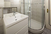Bathroom with tiles and a large shower. Nobody inside