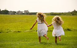 Two young girls running on a green lawn in The Hamptons
