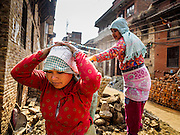 01 MARCH 2017 - KHOKANA, NEPAL: Women carry rocks into a construction site to rebuild a home destroyed in the 2015 earthquake. Recovery seems to have barely begun nearly two years after the earthquake of 25 April 2015 that devastated Nepal. In some villages in the Kathmandu valley workers are working by hand to remove ruble and dig out destroyed buildings. About 9,000 people were killed and another 22,000 injured by the earthquake. The epicenter of the earthquake was east of the Gorka district.     PHOTO BY JACK KURTZ