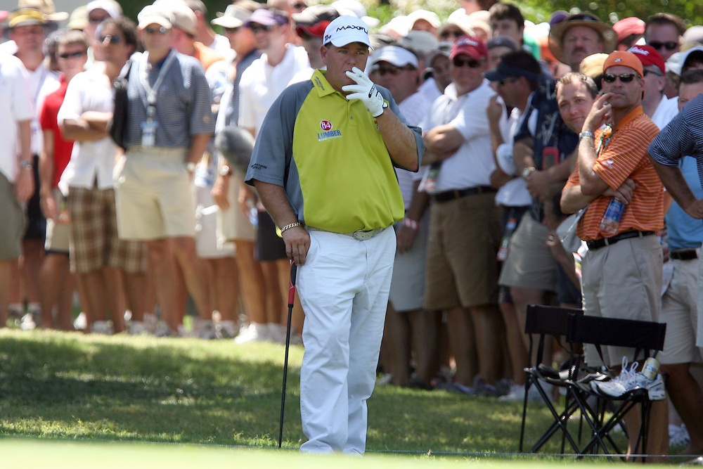 10 August 2007: John Daly smokes a cigarette while waiting to chip out of the rough on the 10th hole during the second round of the 89th PGA Championship at Southern Hills Country Club in Tulsa, OK.