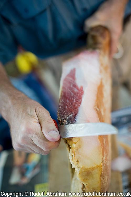 Man cutting prsut (prosciutto) in the village of Jovici, near Zadar, Croatia
