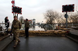 © Licensed to London News Pictures. 28/12/2015. Cawood, UK. A member of the armed forces walks past Sandbags on the bridge over river Ouse at Cawood in North Yorkshire where flood water and rising tides have threatened the town. Several warnings of risk to life are sill in place in parts of Lancashire and Yorkshire where rainfall has been unusually high, causing heavy flooding. Photo credit: Ben Cawthra/LNP