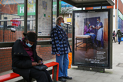 © Licensed to London News Pictures. 20/03/2021. London, UK. Commuters wearing face coverings at a bus stop next to the 'It's about our healthcare' the Office for National Statistics (ONS) Census Day 2021 poster in north London. The Census Day is on 21 March 2021. Every household located in England, Wales and Northern Ireland is legally obligated to fill out the survey or could be fined up to £1,000. The ONS is planning on publishing the initial findings from the Census in March 2022, followed by the full results covering all Census data in March 2023. Photo credit: Dinendra Haria/LNP