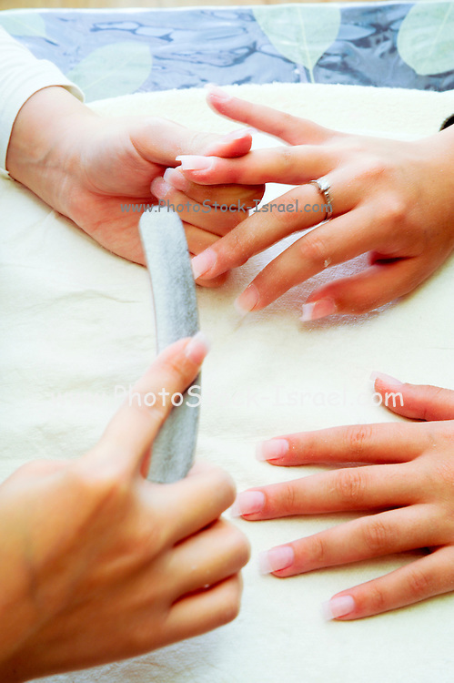 Woman receiving manicure, nail polish is applied, close-up