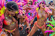 Dancers in costume dance behind their float - Notting Hill Carnival the annual event on the streets of the Royal Borough of Kensington and Chelsea, over the August bank holiday weekend. It is led by members of the British West Indian community, and attracts around one million people annually, making it one of the world's largest street festivals.