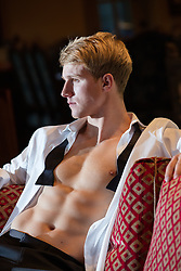 sexy man in an open tuxedo shirt with tie at home